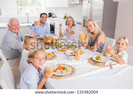Family raising their glasses at thanksgiving and looking at camera