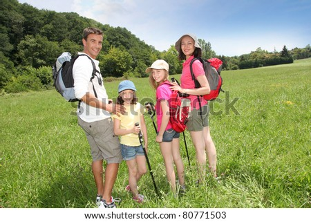 Family rambling in country field - stock photo