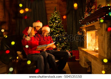 Family read Christmas book sitting on coach in front of fireplace in festive decorated interior