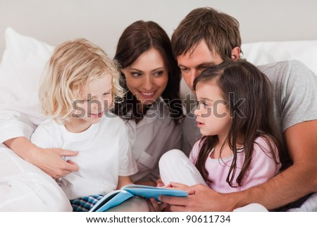 Family reading a book in a bedroom
