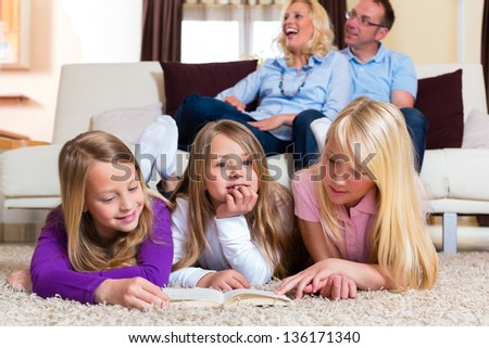 Family reading a book together at home in their living room - stock photo
