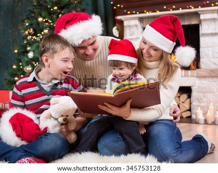 Family reading a book together in front of Christmas tree - stock photo