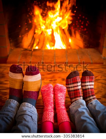 Family relaxing at home. Feet in Christmas socks near fireplace. Winter holiday concept - stock photo