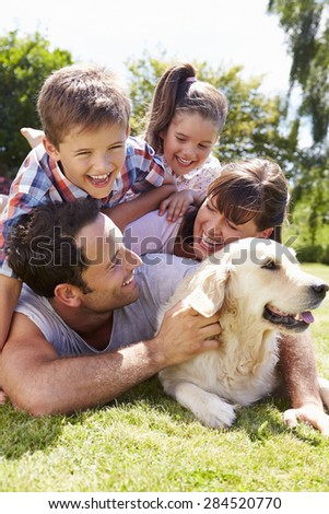 Family Relaxing In Garden With Pet Dog - stock photo