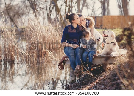 Family Relaxing In Garden With Pet Dogs and puppies. family, pet, animal and people - happy family with labrador retriever dog walking by the river. Happy family playing with their dog on a sunny day - stock photo