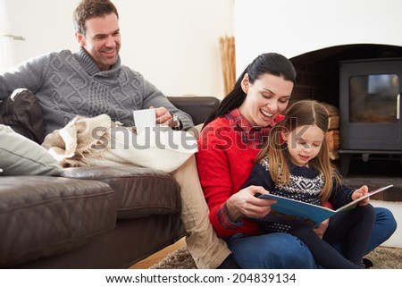 Family Relaxing Indoors And Reading Book - stock photo