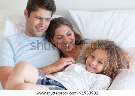 Family relaxing on a bed together - stock photo
