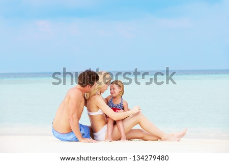 Family Relaxing On Beautiful Beach Together