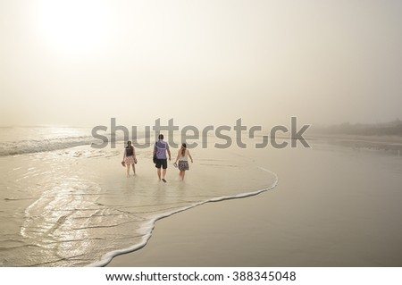 Family relaxing on beautiful foggy beach at sunrise, Daytona Beach, Florida, USA. - stock photo