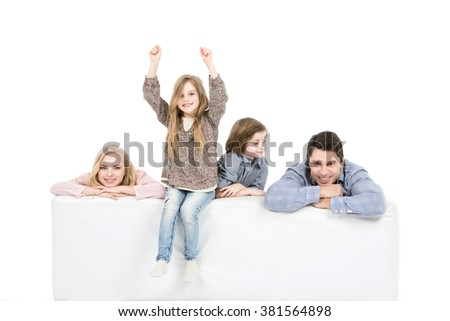 Family relaxing on sofa. Parents with children on the couch isolated on white background. - stock photo