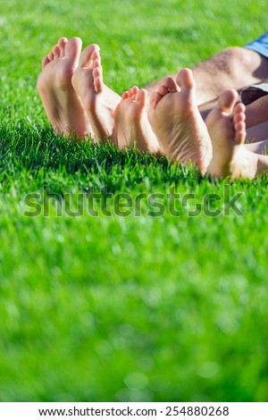 Family relaxing on the grass - stock photo