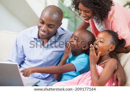 Family relaxing together on the sofa using laptop at home in the living room - stock photo