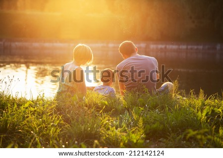 family resting at sunset in the park - stock photo