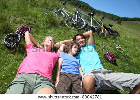 Family resting in nature during bike ride - stock photo