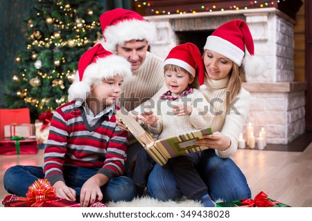 Family reviewing photos in album together near Christmas tree in front of fireplace
