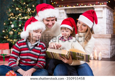 Family reviewing photos in album together near Christmas tree in front of fireplace - stock photo