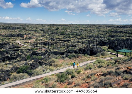Family reviews the information on the boards on the walkway through lava fields at Valley of  Fires Recreation Area,  Carrizozo, New Mexico - stock photo