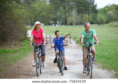 Family riding bicycles in countryside - stock photo