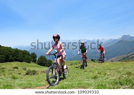 Family riding bikes in the mountains - stock photo