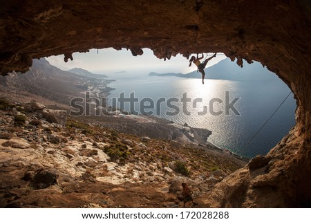 Family rock climber against picturesque view of Telendos Island at sunset. Kalymnos Island, Greece.  - stock photo