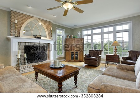 Family room in luxury home with large brick fireplace - stock photo