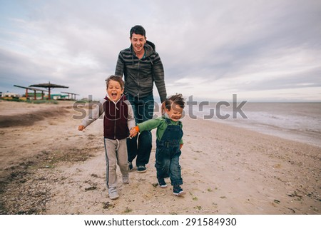 Family running on beach holding hands smiling - stock photo