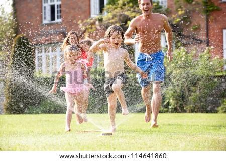 Family Running Through Garden Sprinkler - stock photo