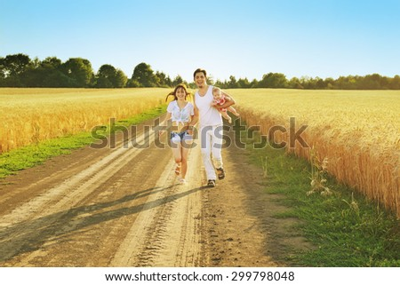Family Running Together Through Summer Harvested Field. Happy family enjoying and running together outdoors. Mother, father and little baby girl. - stock photo
