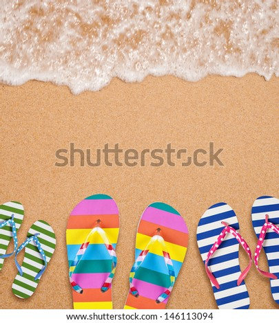 Family's flip flop pairs on sea surf with copy space for your text - stock photo