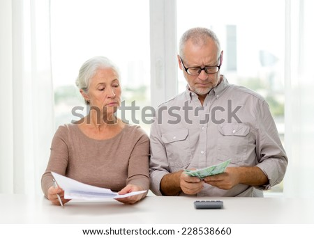 family, savings, age and people concept - senior couple with papers, money and calculator at home - stock photo