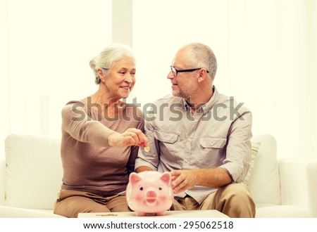 family, savings, age and people concept - smiling senior couple with money and piggy bank at home - stock photo