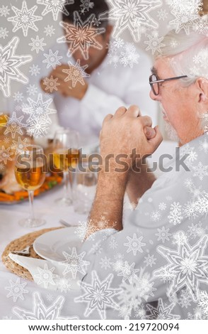 Family saying grace before eating against snowflakes on silver - stock photo