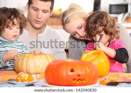 Family sculpting pumpkins - stock photo