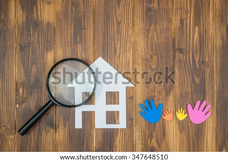 family Searching house conceptual, paper house with Magnifier on wooden background - stock photo