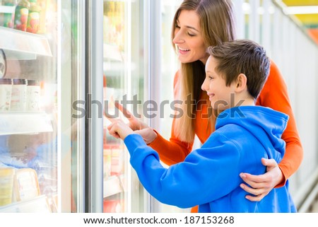 Family selecting frozen products while grocery shopping in supermarket  - stock photo
