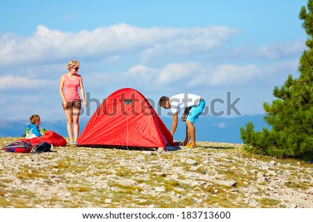 family set up a camp in mountains, active lifestyle - stock photo
