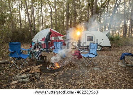 family setting up campsite at sunset with tent and teardrop trailer - stock photo