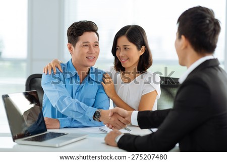 Family shaking hands with real estate broker after successful deal - stock photo