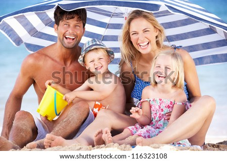 Family Sheltering From Sun Under Beach Umbrella - stock photo