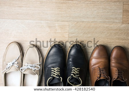 Family shoes on wooden background. Top view.