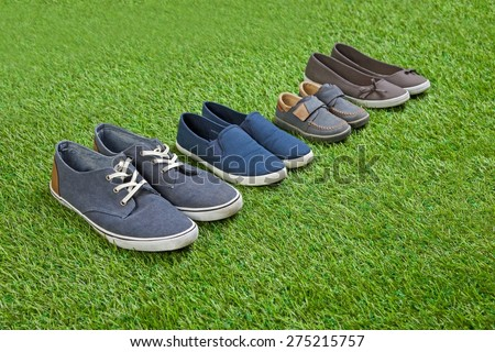 Family shoes standing  on green summer grass in a row