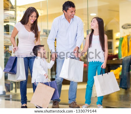 Family shopping at the mall and looking very happy - stock photo