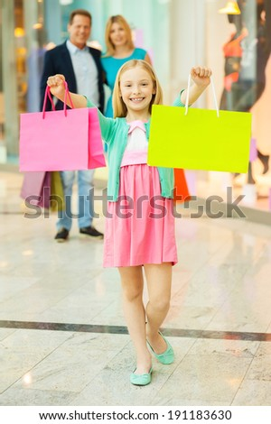 Family shopping. Cheerful family shopping in shopping mall while little girl showing her shopping bags and smiling - stock photo