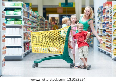 Family shopping. Woman and children with shop cart in supermarket store - stock photo