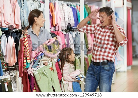 Family shopping. Woman and girl holding clothes with highly surprised father man during shopping at outerwear supermarket - stock photo