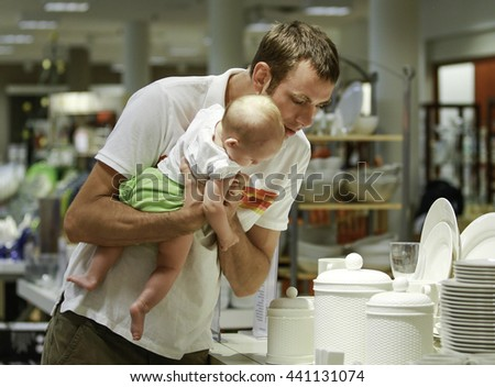Family shopping. Young father and his daughter on hands in the mall. He shows something  - stock photo
