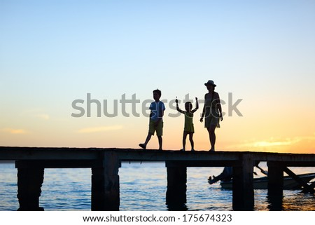 Family silhouettes on a bridge at sunset