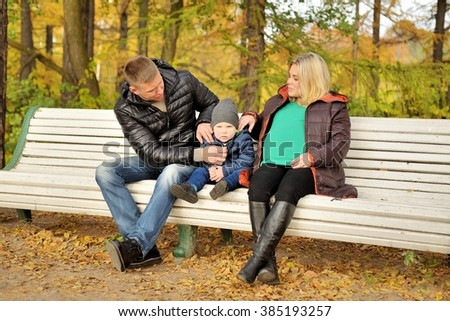 Family sits in autumn park on bench
