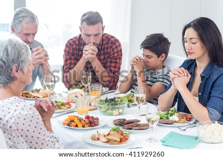 Family sitting at dining table and praying together before meal - stock photo