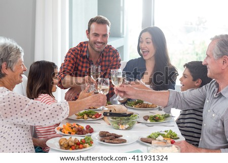 Family sitting at dining table having meal - stock photo